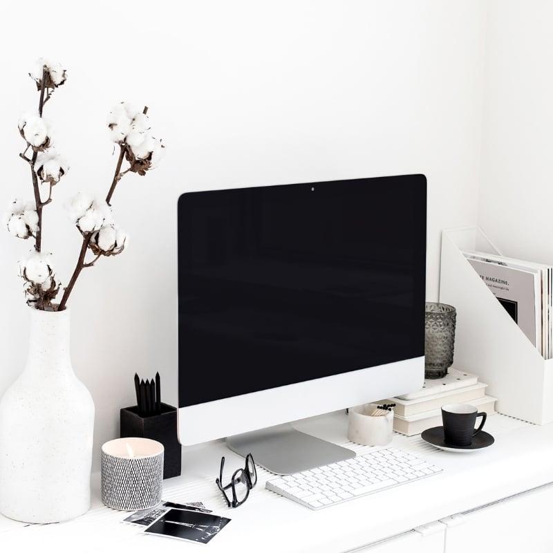 Computer on white desk with white desk accessories