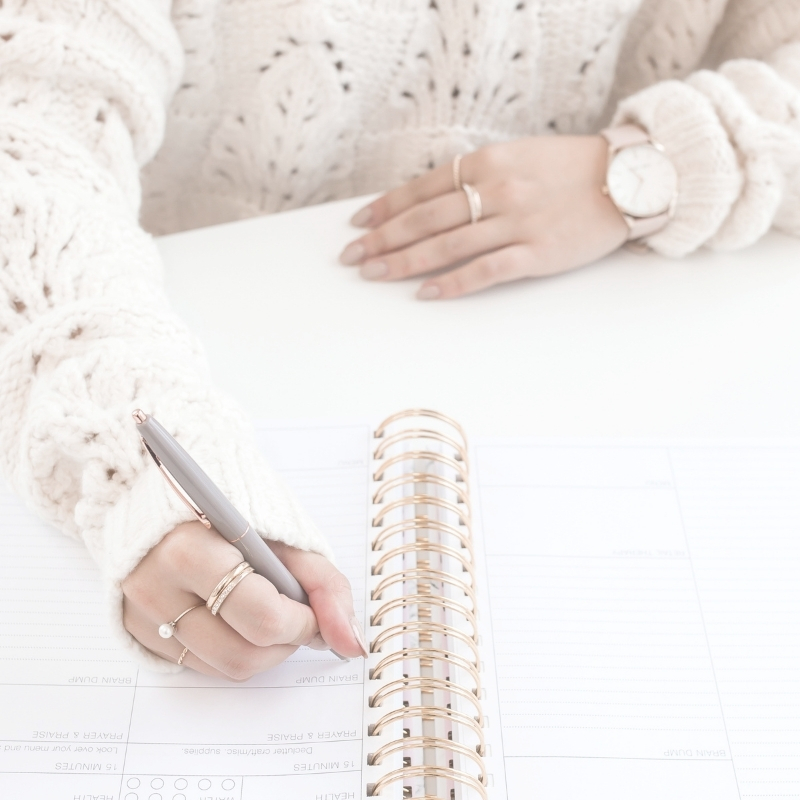 Lady in cream jumper writing in a spiral bound notebook
