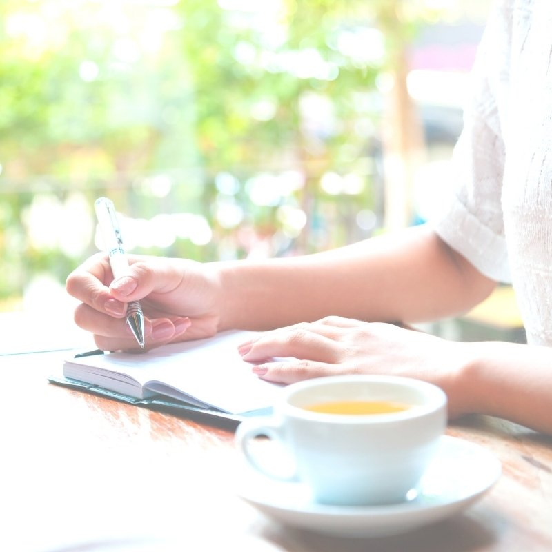 Lady at a desk writing in a planner with a cup pf tea by her side
