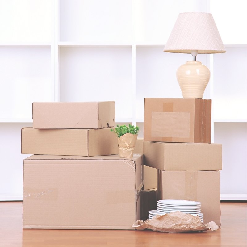 Boxes for moving house in a pile with a lamp on top