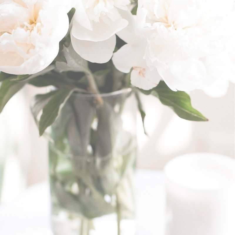Vase of white flowers and white candle