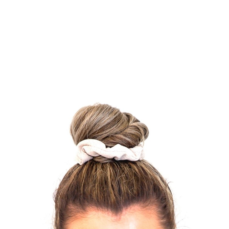 Top of ladies head with top knot in white hair band
