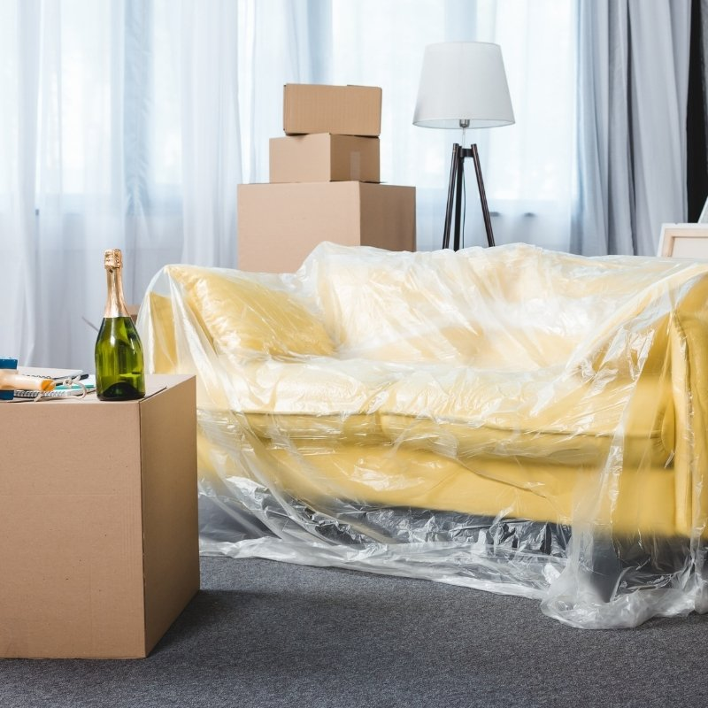 yellow sofa under plastic with moving boxes by the side