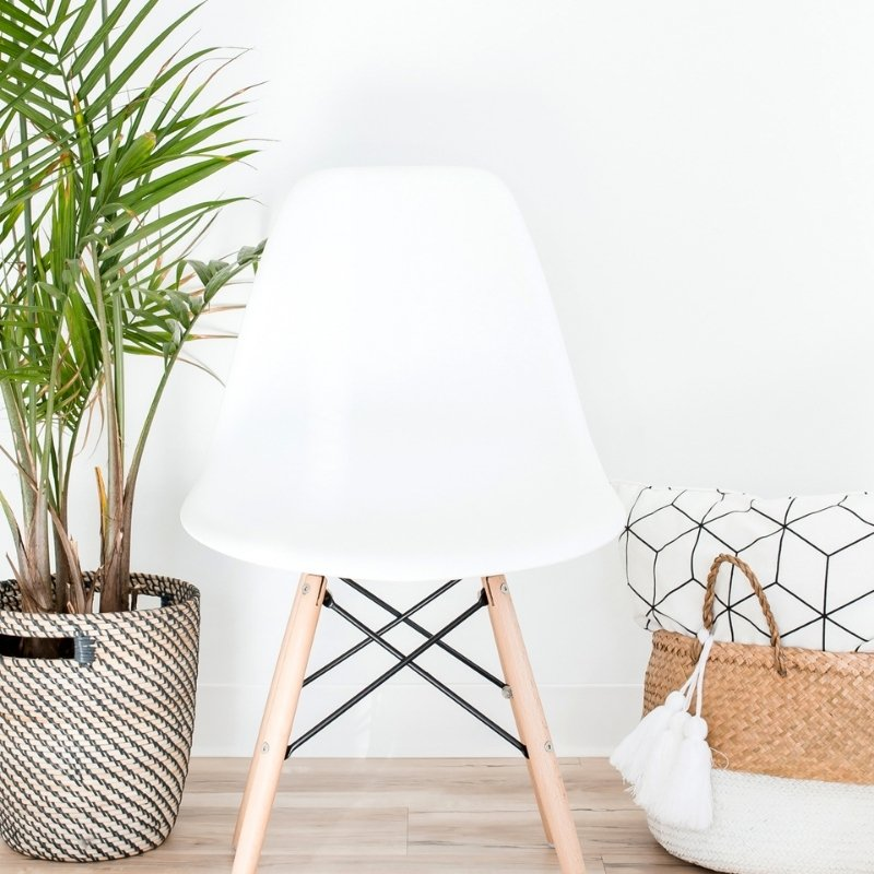 Living room with white chair, plant in pot, and basket full of cushions and throws