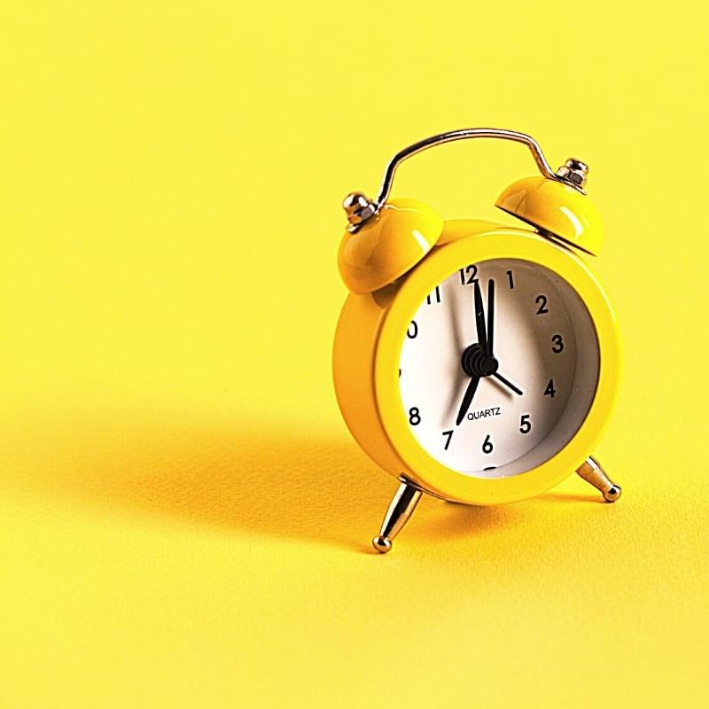 Yellow alarm clock on yellow background