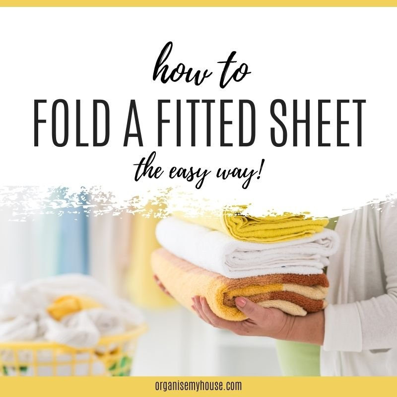 Lady holding folded laundry with title words overlaid (How to fold a fitted sheet the easy way)