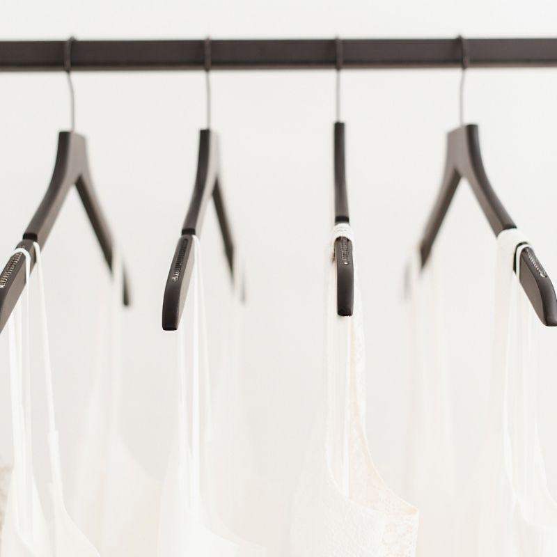 white clothes on black coat hangers on black rail