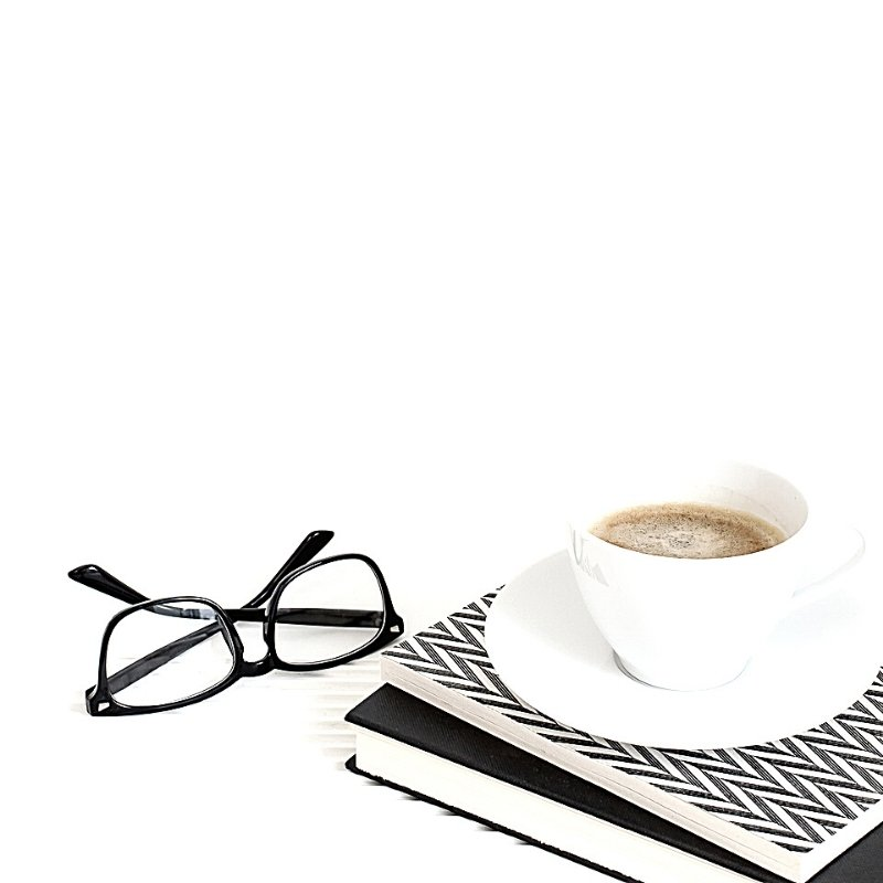 White background with cup of coffee on black and white books and a pair of black glasses by the side