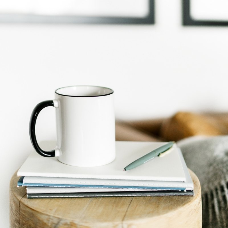 Coffee table with notebooks on top and coffee cup on top of it all