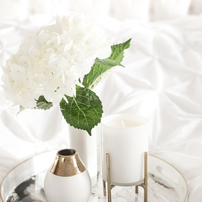 White bedding with tray of flowers and candles on top