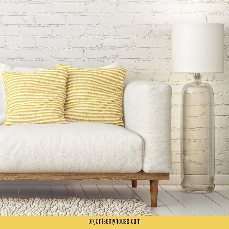 White sofa with yellow cushions on it