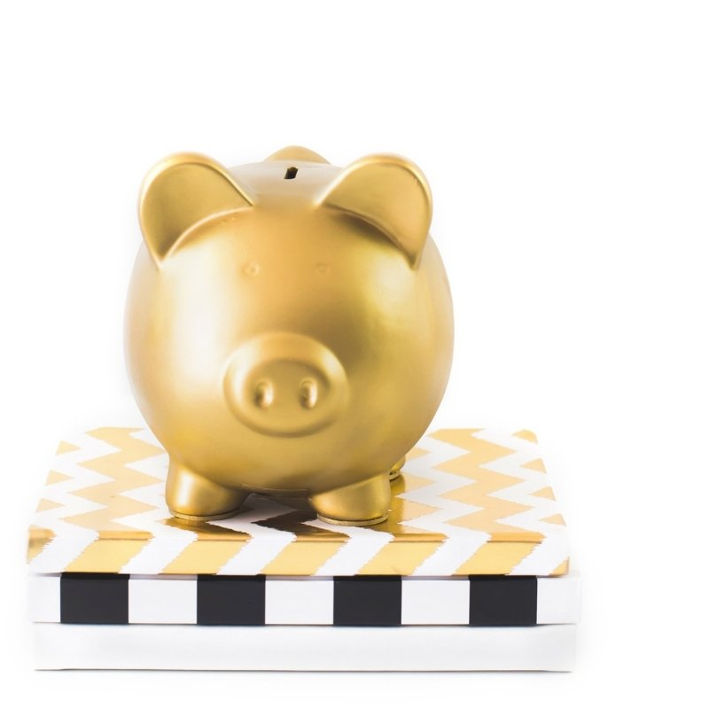 Gold piggy bank on top of a pile of books