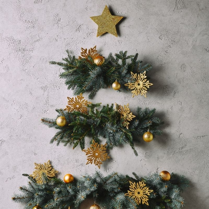 Christmas tree made with pieces of foliage and baubles stuck on a wall with star on top