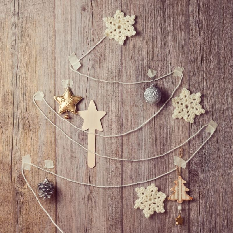 Christmas tree design made of string on a wall with baubles