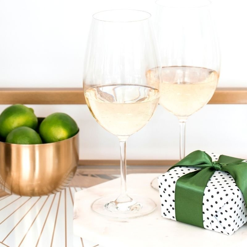 Table with white wine, a bowl of limes, and a gift on it