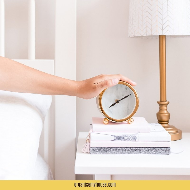 Hand reaching for alarm clock from bed