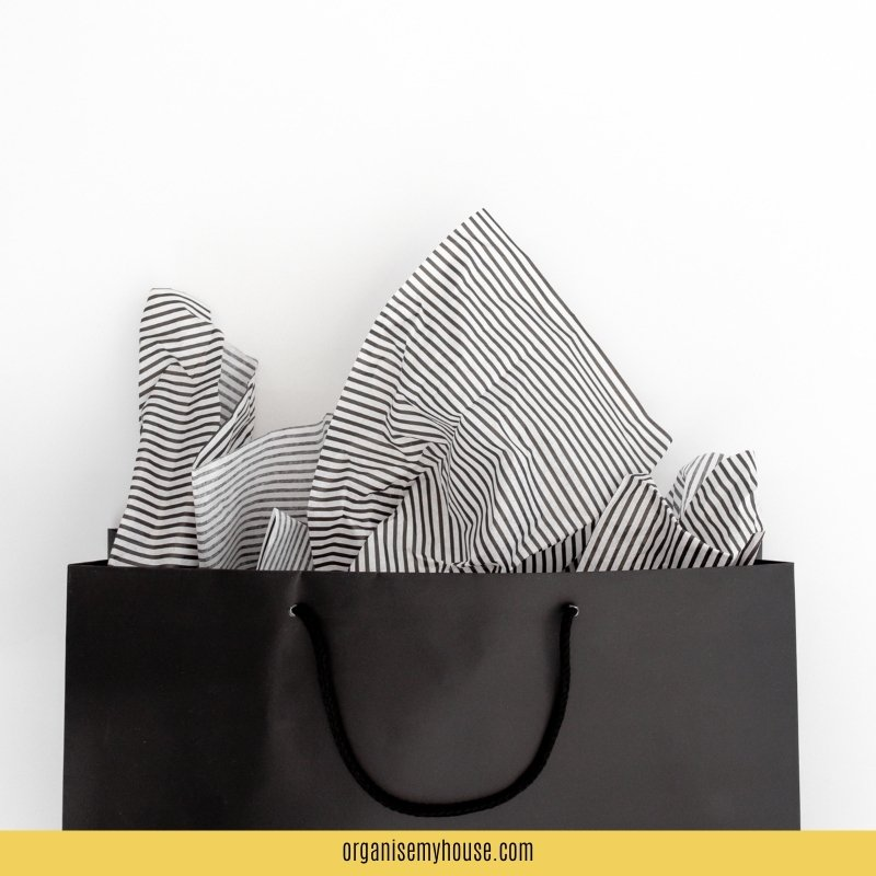 Black gift bag with black and white tissue paper sticking out of the top