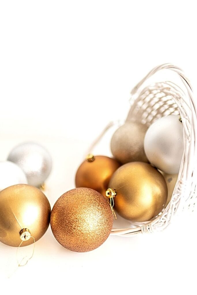 white and gold baubles spilling out of white basket
