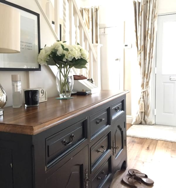 Black sideboard in a hallway
