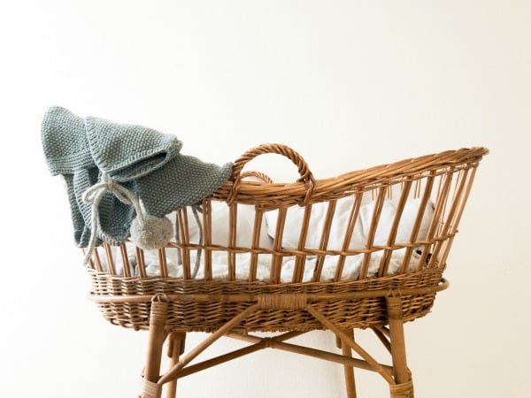 Wicker cot with blue knitted baby clothes draped over