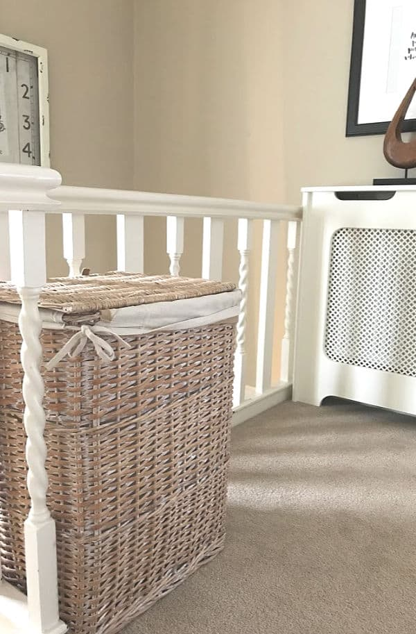 Wicker Landry basket on a landing in a cream colour scheme with a white radiator cover in the background