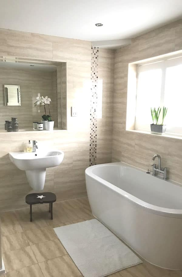 Neutral Bathroom tiles with a large mirror above the sink and a large window above the bath