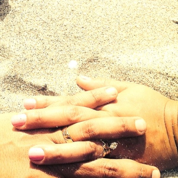 Closeup of holding hands on a beach
