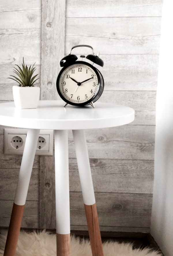 Black alarm clock on white bedside table with wood background