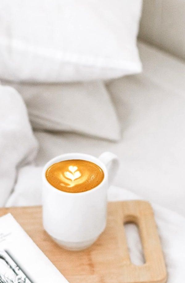 Coffee mug on white bedding