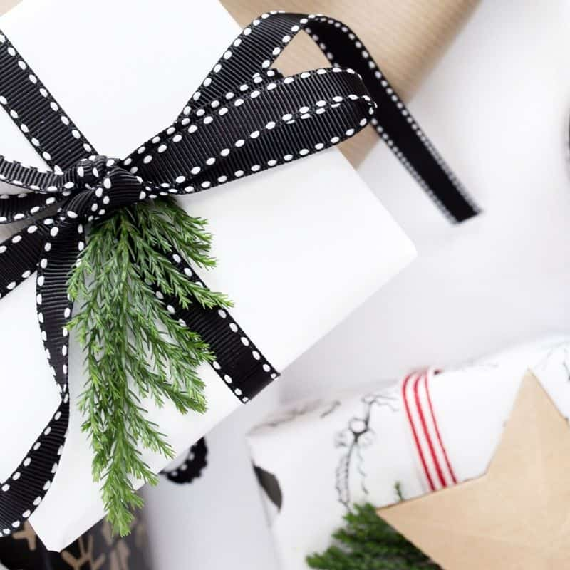 Black and White Christmas Presents with Greenery. Brown Star Label with red tags as well.