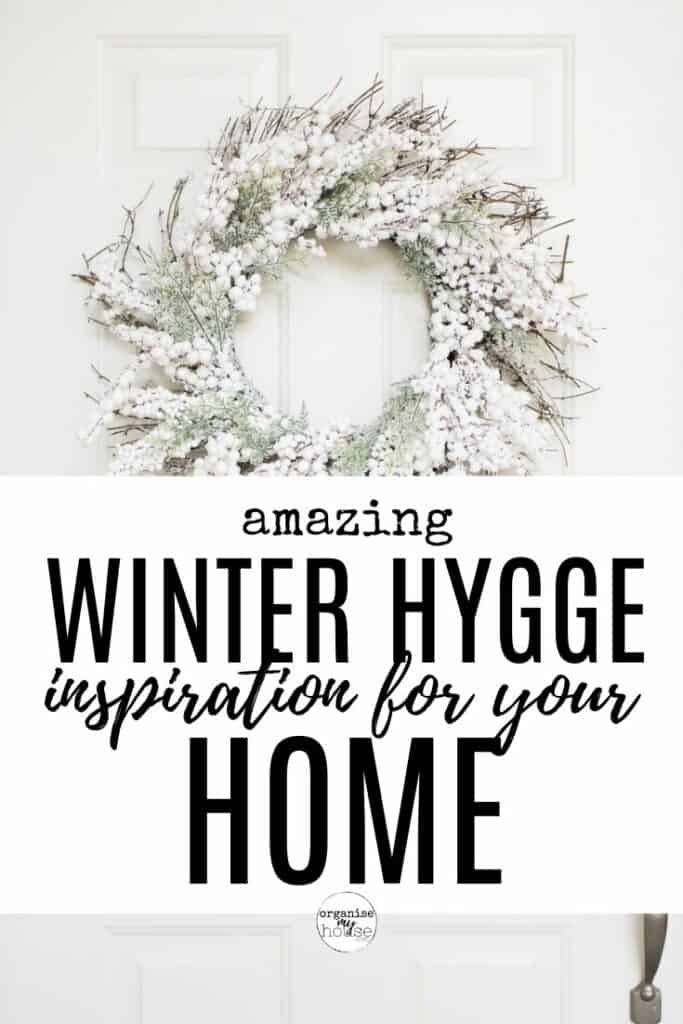 """White front door with wreath on - with post title wordinng overlaid """"winter Hygge Ideas for your home"""""""