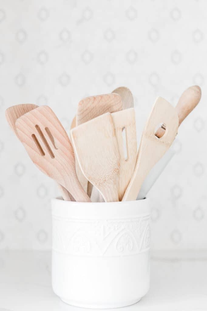 White kitchen utensil pot and wooden utensils inside