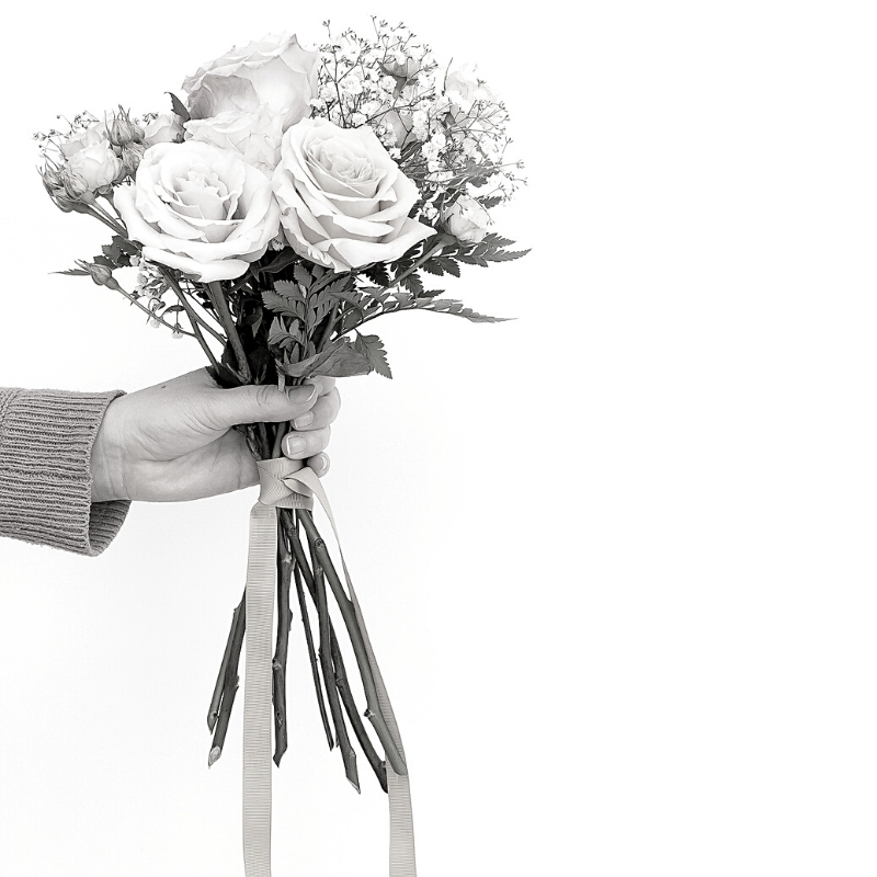 Black and white picture of hand holding ribbon tied bunch of flowers