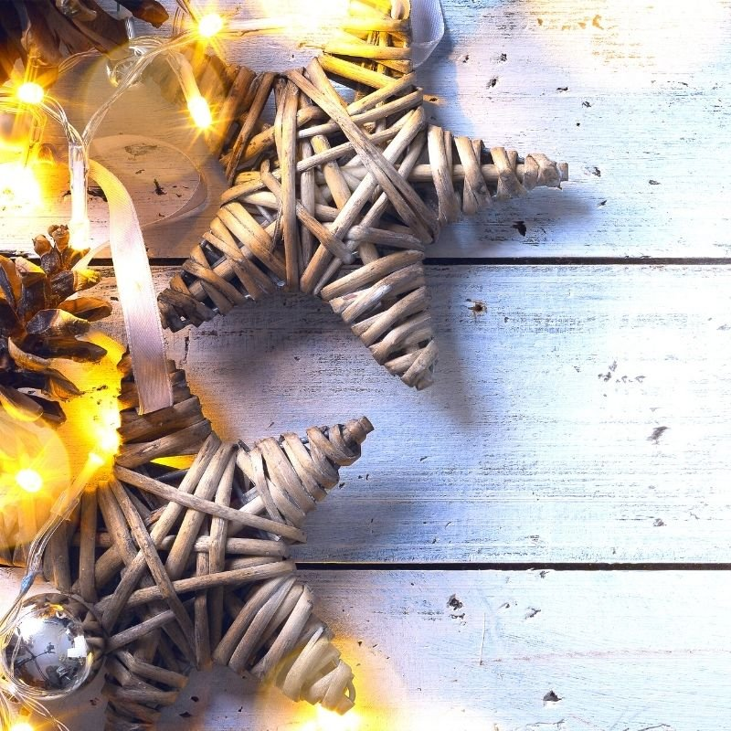 Starts and Christmas lights on white wooden background