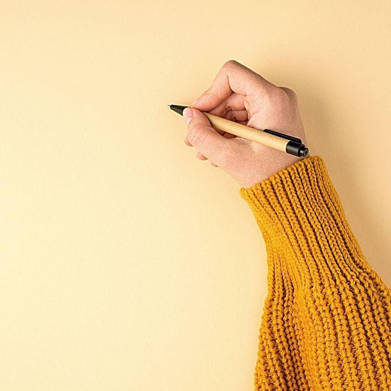 Arm in Orange jumper with pen in hand