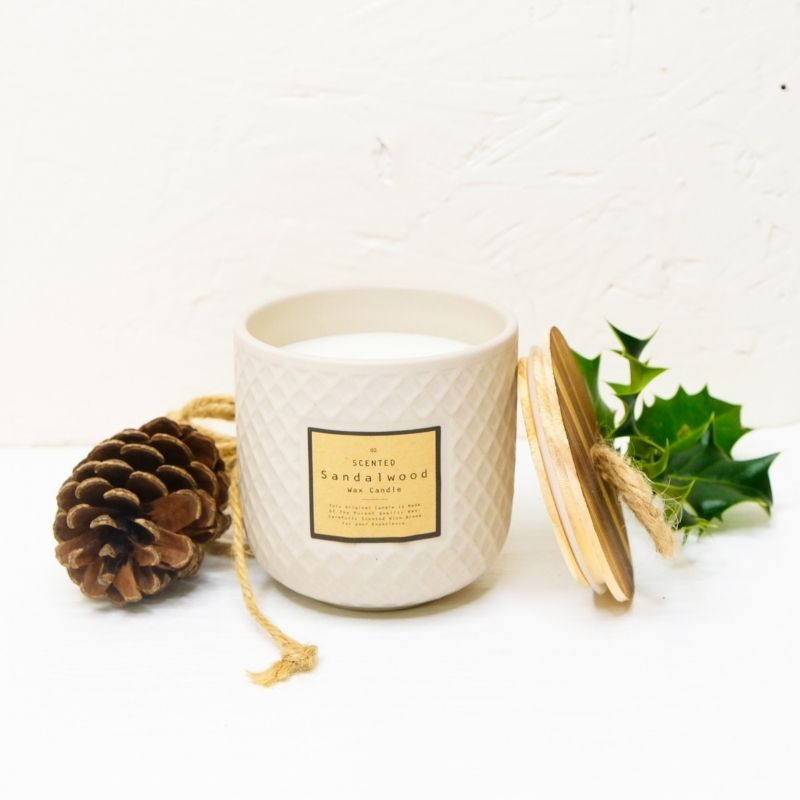 Candle with Christmas items around it like fir cones