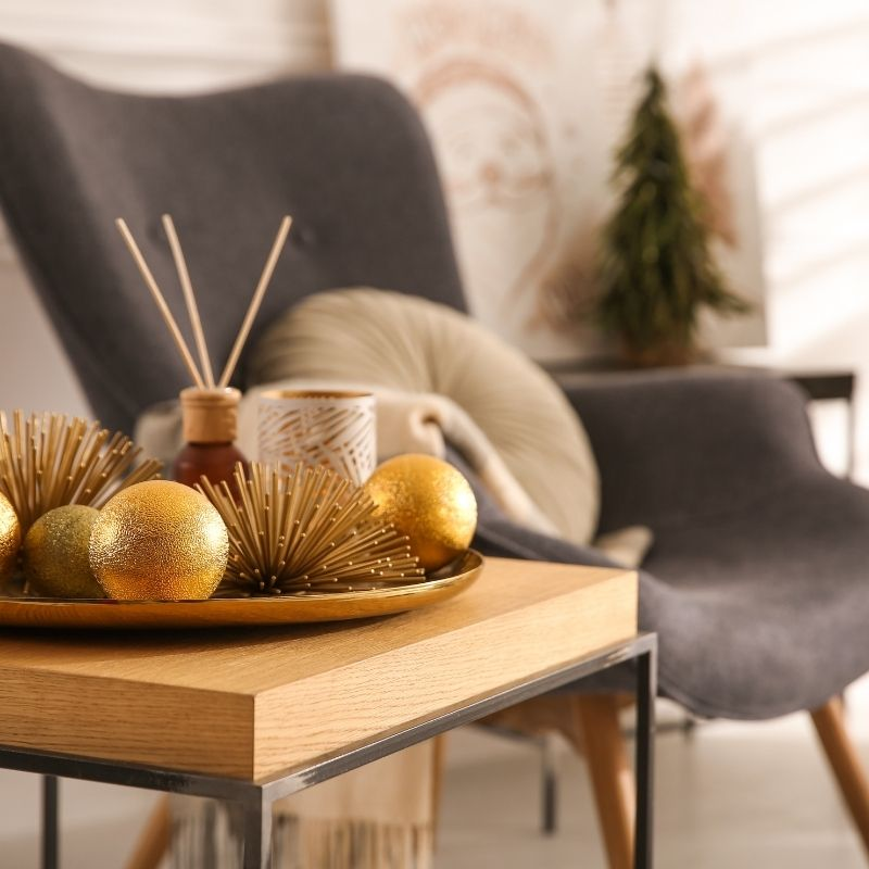 Gery armchair in background with diffuser and gold baubles on table in foreground