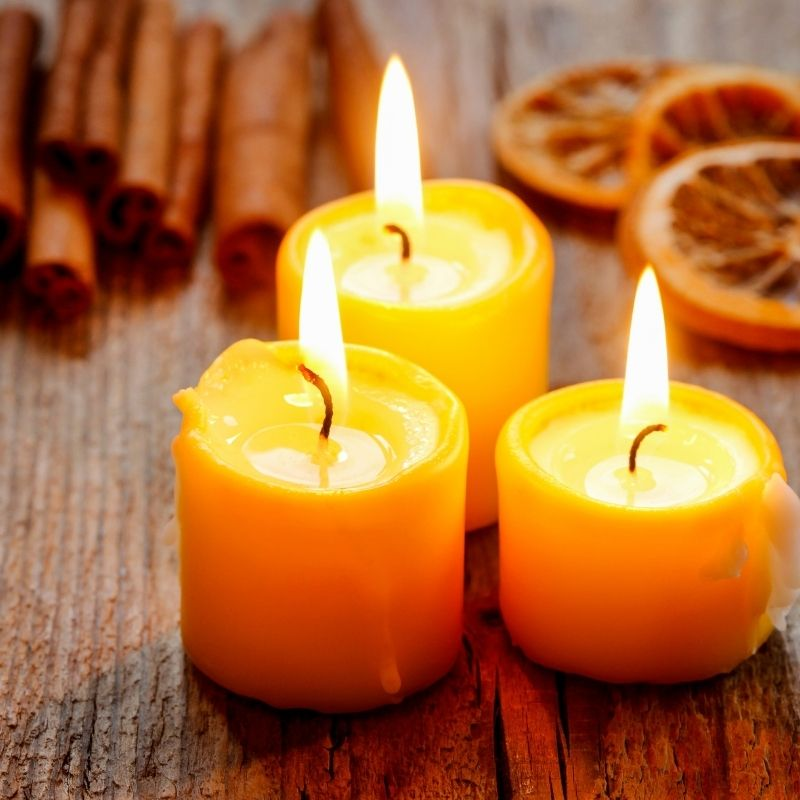 3 lit candles with dried oranges and cinnamon sticks on a tables